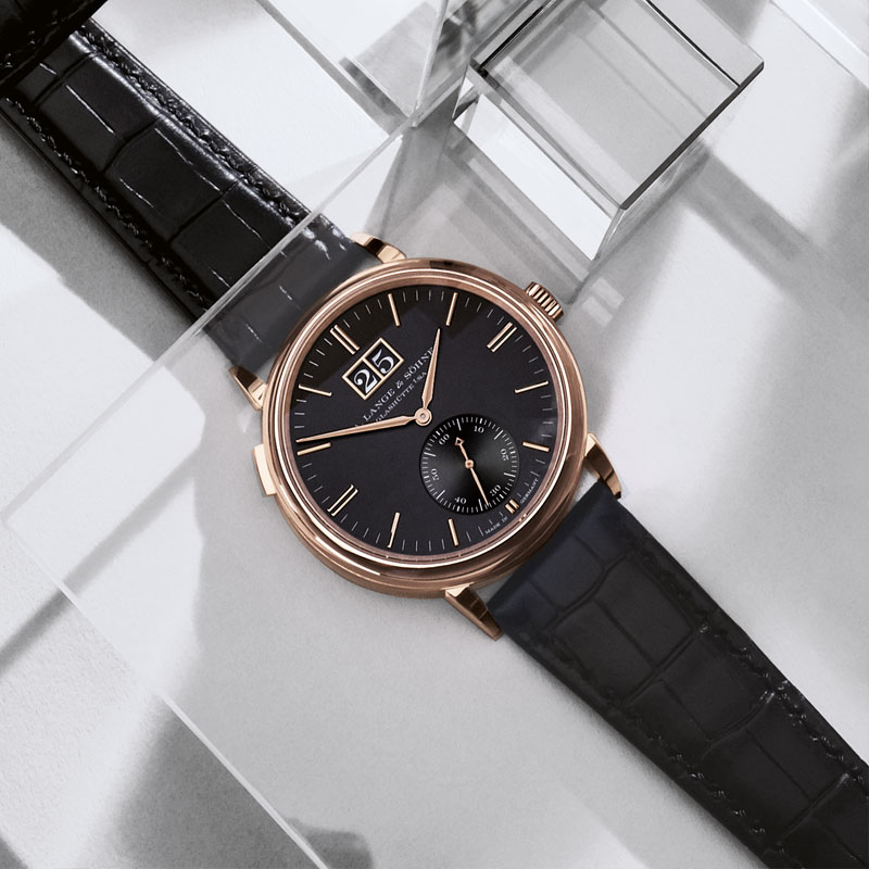 The 18k rose gold copy watch has black dial.